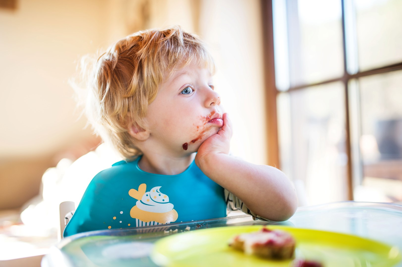 A cute toddler boy eating at home.