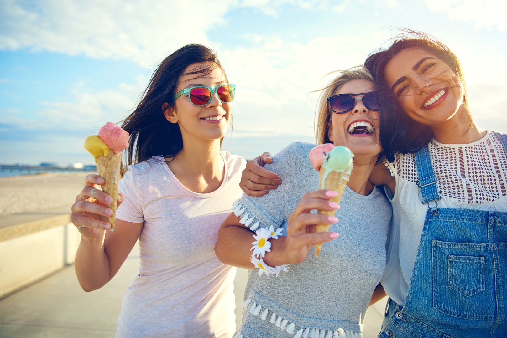 Laughing teenage girls eating ice cream cones as they walk along a beachfront promenade arm in arm enjoying their summer vacation