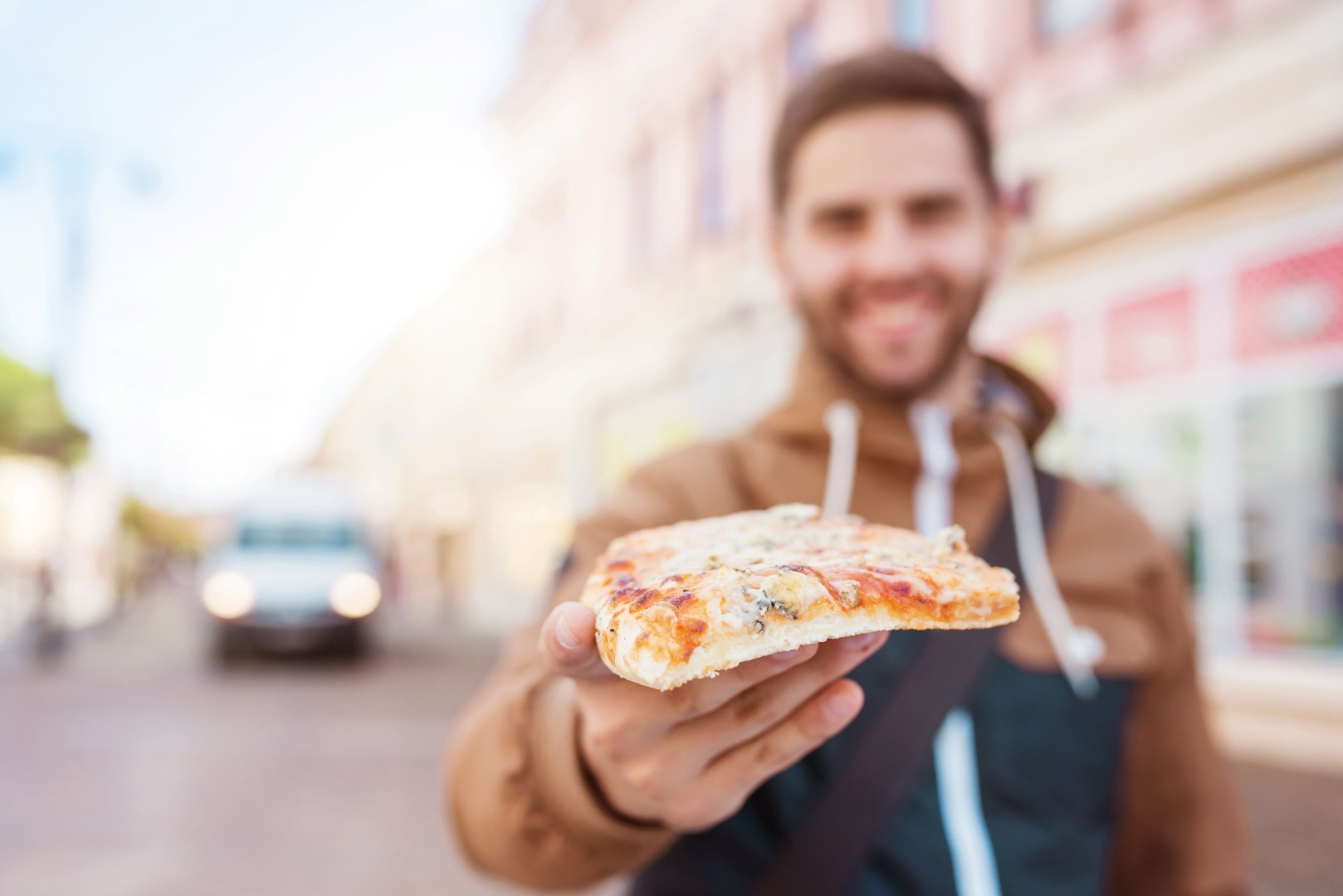 Handsome young man eating a slice of pizza outside on the street